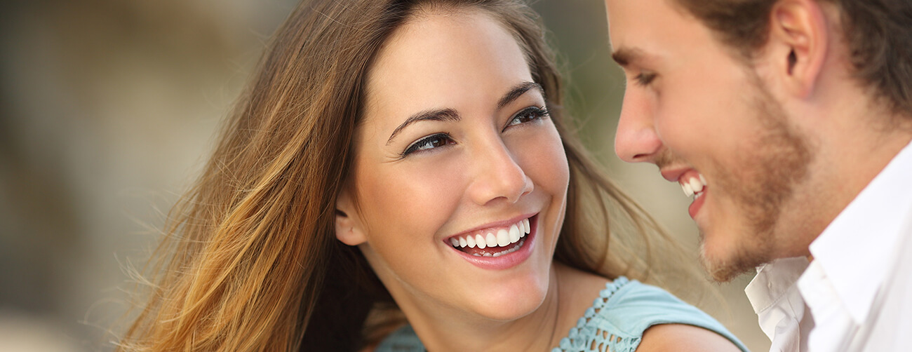 an attractive young woman with a beautiful smile is looking at her friend