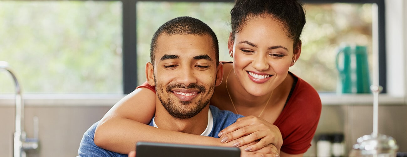 a young couple is looking at a tablet and smiling
