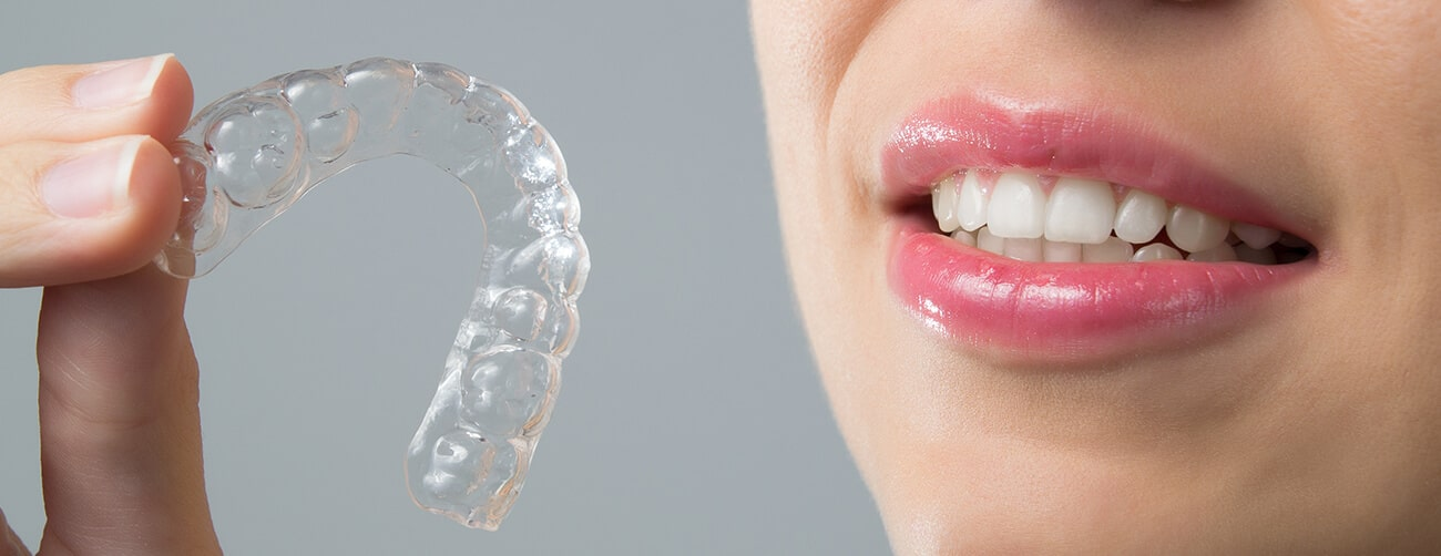 woman is holding invisalign braces