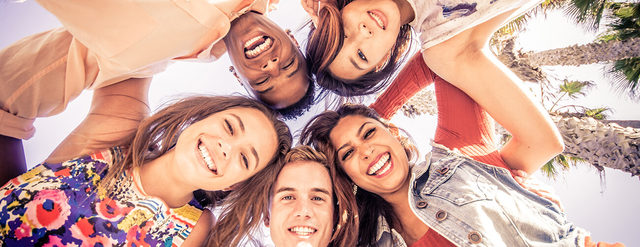 a group of friends in a circle looking down and smiling