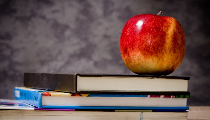 A red apple sits atop a stack of three college textbooks in front of a gray wall