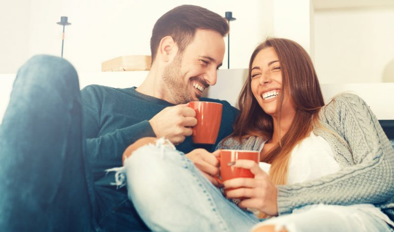 A man and woman with dental implants smile as they cuddle on a couch while holding orange mugs