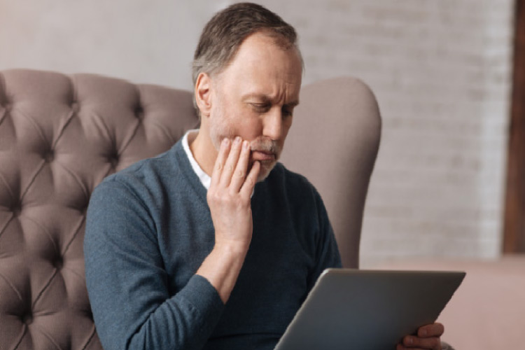 man holds his painful jaw while researching tooth infection on his laptop