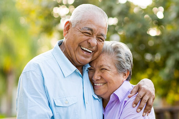 senior couple hugging and smiling after learning about dentures