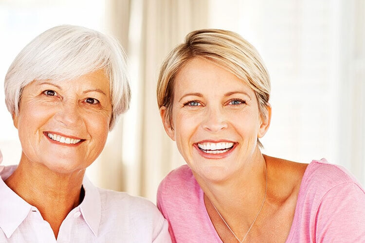 two women smile to show off their veneers and lumineers